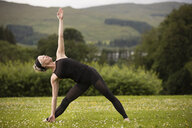 Mature woman practicing yoga cow face pose in field - CUF32629