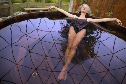 Mature woman lying back in hot tub at eco retreat - CUF32638