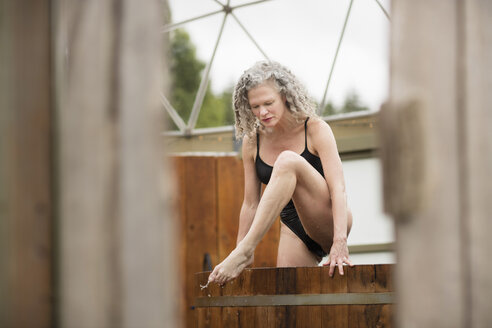 Mature woman stepping out of hot tub at eco retreat - CUF32641