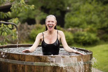 Mature woman standing in fresh cold water tub at eco retreat - CUF32644