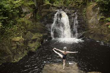 Rear view of mature woman practicing yoga in front of waterfall - CUF32647