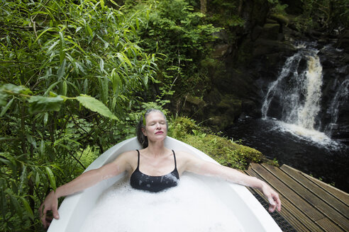 Mature woman relaxing in bubble bath in front of waterfall at eco retreat - CUF32650
