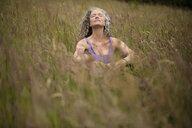 Mature woman sitting in long grass meditating - CUF32653