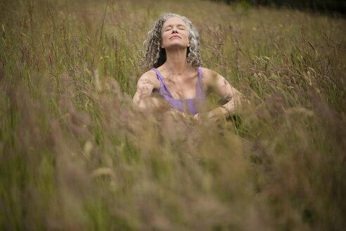 Mature woman sitting in long grass meditating - CUF32653