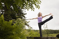 Mature woman practicing yoga pose on footbridge - CUF32656