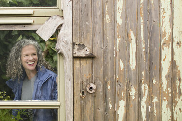 Smiling mature woman looking out of greenhouse window - CUF32659
