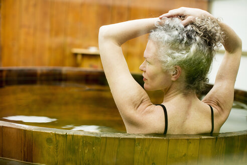 Mature woman with hands in hair in hot tub at eco retreat - CUF32662