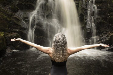 Rear view of mature woman practicing yoga pose in front of waterfall - CUF32665