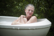 Mature woman hugging knees in garden bubble bath at  eco retreat - CUF32668