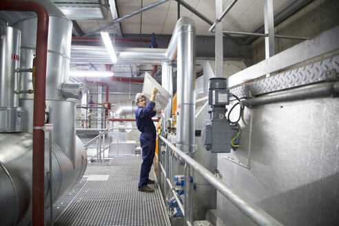 Engineer removing cover from equipment in power station - CUF32800