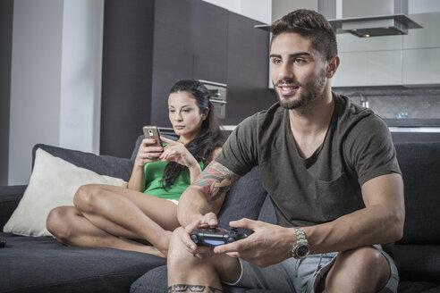 Young couple on sofa using smartphone and gaming control - CUF32961