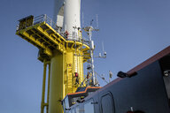 Engineers climbing wind turbine from boat at offshore windfarm - CUF32970