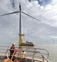 Engineer in boat at offshore windfarm turbine - CUF32976