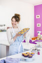 Woman holding up tray of homemade cupcakes - CUF33018