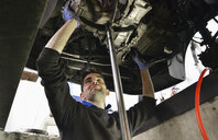 Mechanic checking car undercarriage - CUF33066