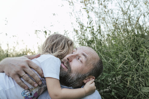 Father and little daughter lying together on a meadow hugging each other - KMKF00359