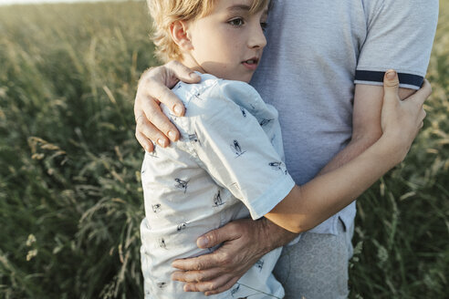 Boy hugging his father on a meadow - KMKF00365