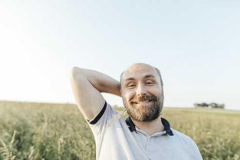 Portrait of mature man pulling funny faces in nature - KMKF00368