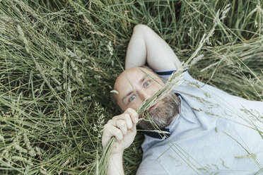 Portrait of mature man lying on grass pulling funny faces - KMKF00371