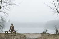 Young woman sitting on bench by misty lake - ISF10561