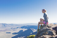 Young female trail runner gazing from rock on Pacific Crest Trail, Pine Valley, California, USA - ISF10591