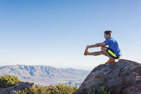 Male trail runner stretching legs on rock on Pacific Crest Trail, Pine Valley, California, USA - ISF10594