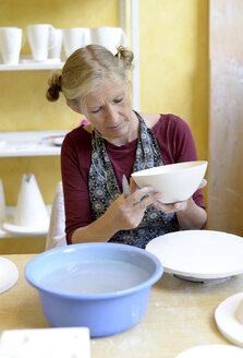 Woman working on bowl in porcelain workshop - BFRF01845