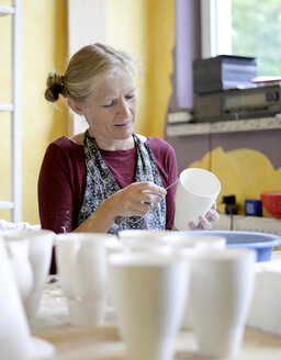 Woman working on mug in porcelain workshop - BFRF01857