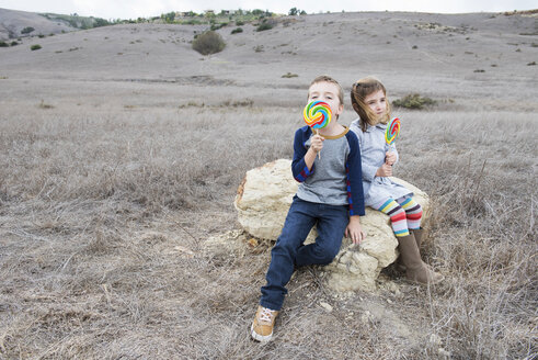 Portrait of brother and sister sitting on rock licking lollipops - ISF10620