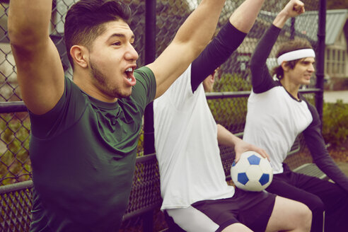 Three male soccer player spectators celebrating - ISF10662