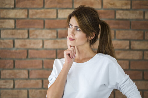 Portrait of thinking young woman in front of brick wall - AWF00057