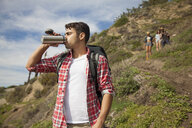 Young man at bottom of hill, drinking from flask, friends trailing behind - ISF10705
