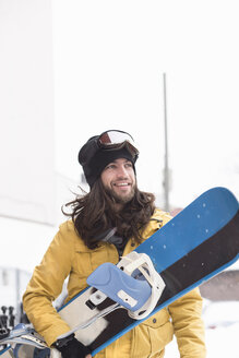 Smiling male snowboarder carrying snowboard in street - ISF10789