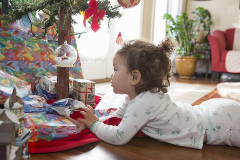 Little girl admiring Christmas ornaments on tree - ISF10804