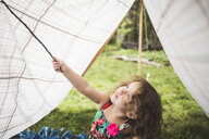 Girl poking homemade garden tent with twig - ISF10861