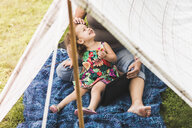 Mature woman and granddaughter sitting in homemade garden tent using digital tablet - ISF10870