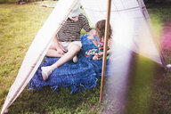 Girl and grandfather playing in homemade garden tent - ISF10885