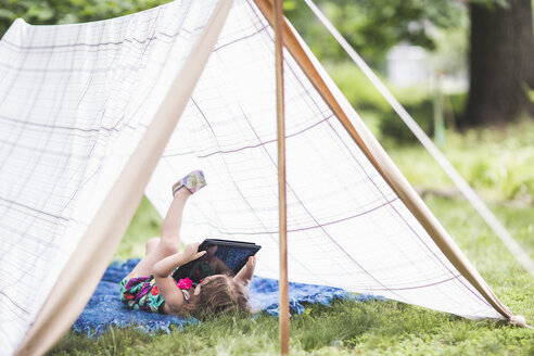 Girl lying on back in homemade garden tent looking at digital tablet - ISF10891
