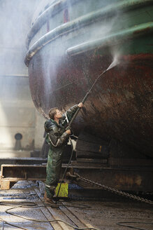 Shipyard worker cleaning boat with high pressure hose - ISF10960