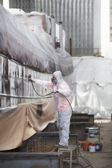 Worker spray-painting boat in shipyard - ISF10966