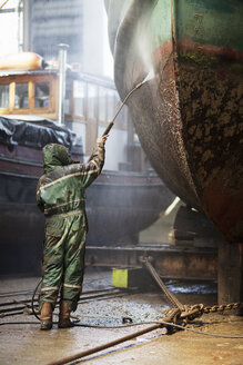 Rear view of worker cleaning boat with high pressure hose in shipyard - ISF11008