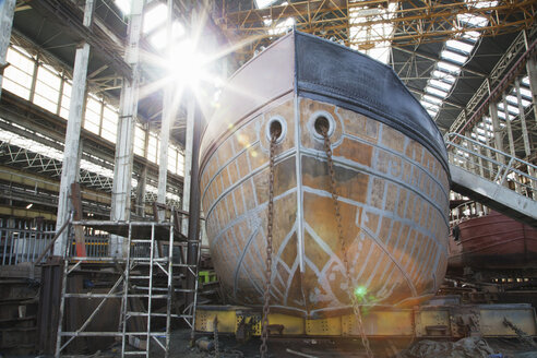 View of sunlit boat hull in shipyard workshop - ISF11011
