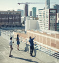 Businesspeople looking and pointing at buildings on roof terrace, Los Angeles, California, USA - ISF11014