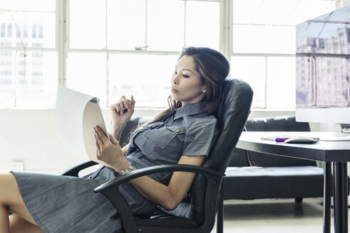 Businesswoman reading notes by office window - ISF11017