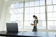 Businesswoman working by office window - ISF11029