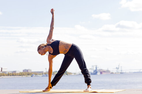 Full length front view of young woman by water in yoga position, Philadelphia, Pennsylvania, USA - ISF11173
