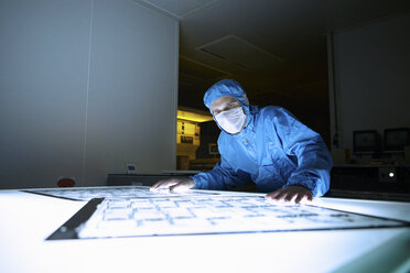 Male worker inspecting flex circuit on lightbox in flexible electronics factory clean room - ISF11269