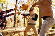 Young woman and two teenage brothers throwing leaves at each other in autumn forest - ISF11362