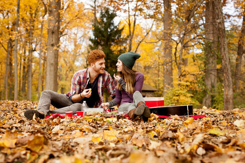 Happy young couple having picnic in autumn forest - ISF11371