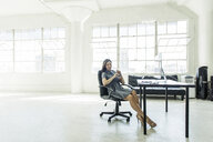 Businesswoman resting on chair by office window - ISF11386